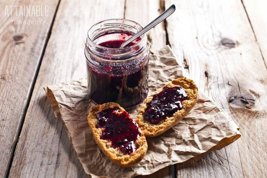 jar of grape jelly with two slices of homemade bread