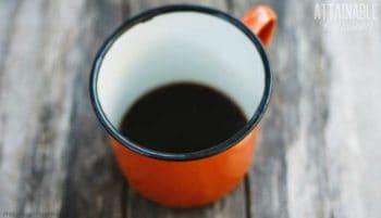 black coffee in an orange tin cup