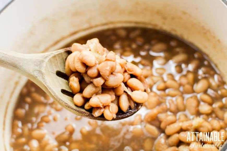 pinto beans cooked in a white pot, with some on a wooden spoon