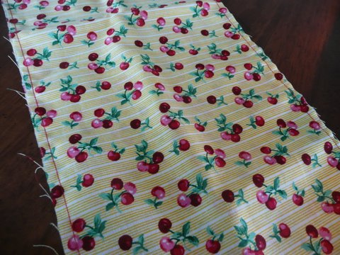 sewing reusable bags from yellow cloth with red cherries