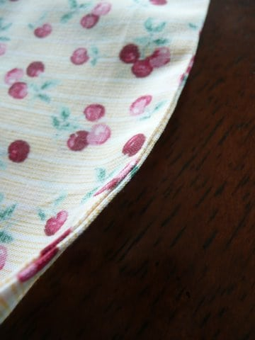 Close up of French seam on cloth bag made from yellow fabric with red cherries