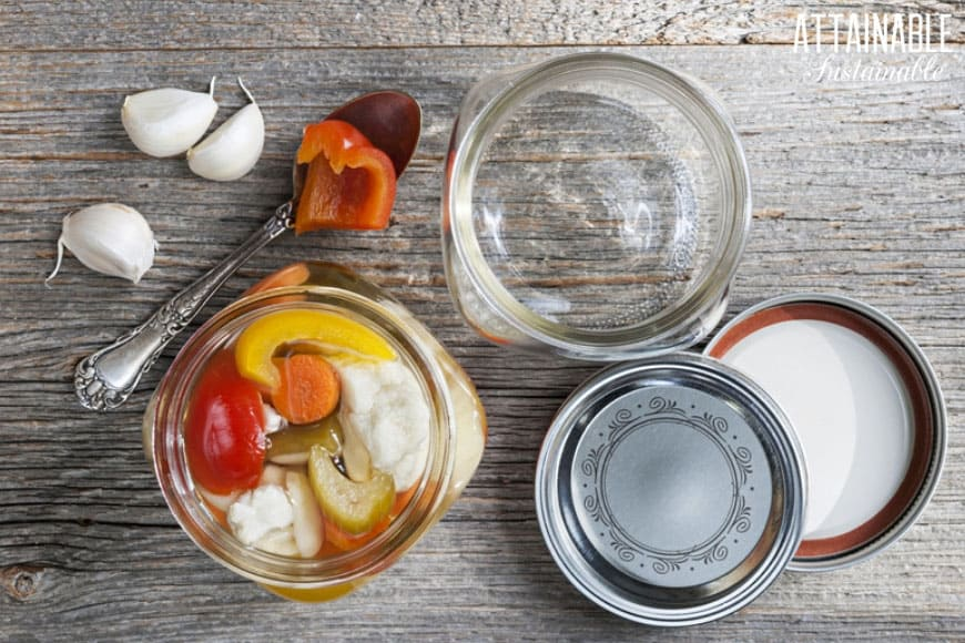 home canning in process: empty canning jar and a canning jar full of vegetables with lids on the table