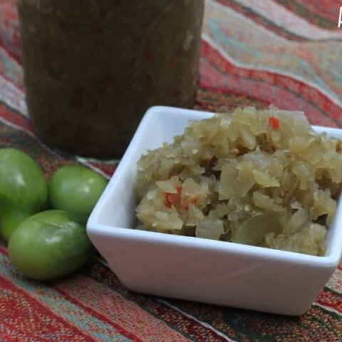 green tomato relish in a square white dish on a red striped background
