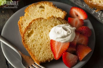 passion fruit cake slices on a plate with strawberries and whipped cream