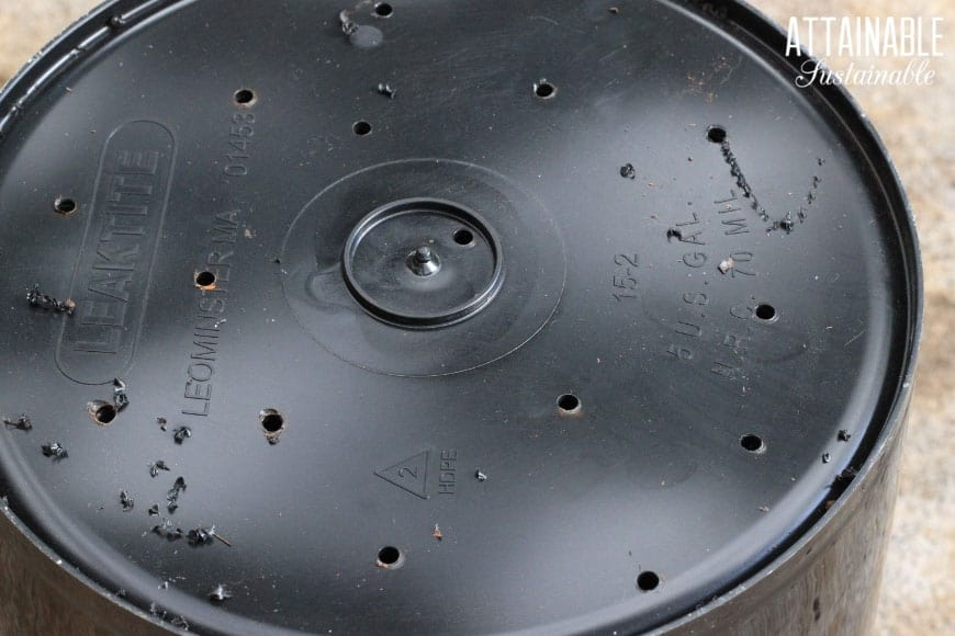 black bucket with holes drilled in bottom
