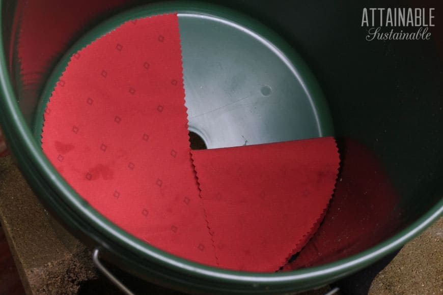 round piece of red fabric in the bottom of a bucket to make an upside down tomato planter
