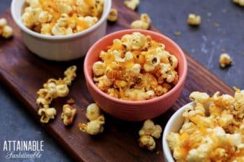 cheddar popcorn snacks in several bowls (on brown board)