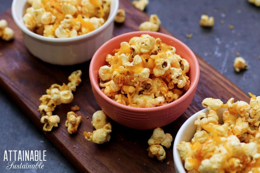cheddar popcorn snacks in several bowls (on brown board)