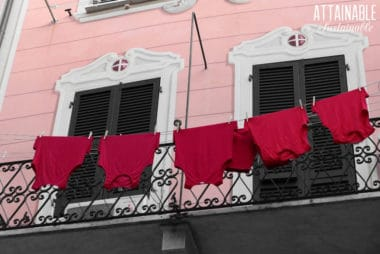 red shirts hanging on a laundry line in front of a pink building.