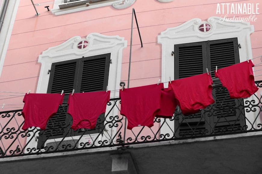red tank tops hanging upside down in front of a pink building. One example of eco conscious living