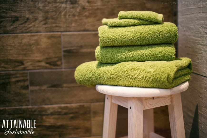 green washcloths stacked on a wooden stool