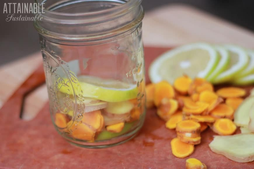 slices of ginger, turmeric, and lemon on a cutting board, with some in a glass jar
