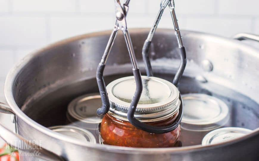 jar lifter putting jar of salsa into canner