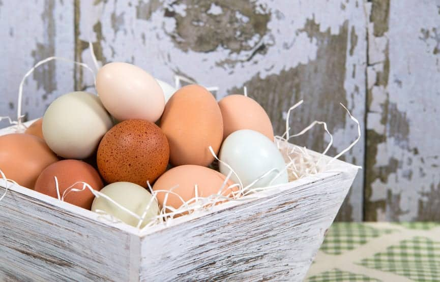 Assortment of different color, fresh, chicken eggs in a wooden container, country style kitchen background