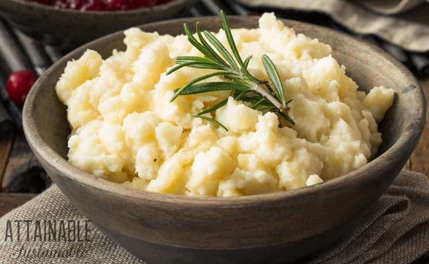 mashed potatoes in a brown bowl with rosemary sprig