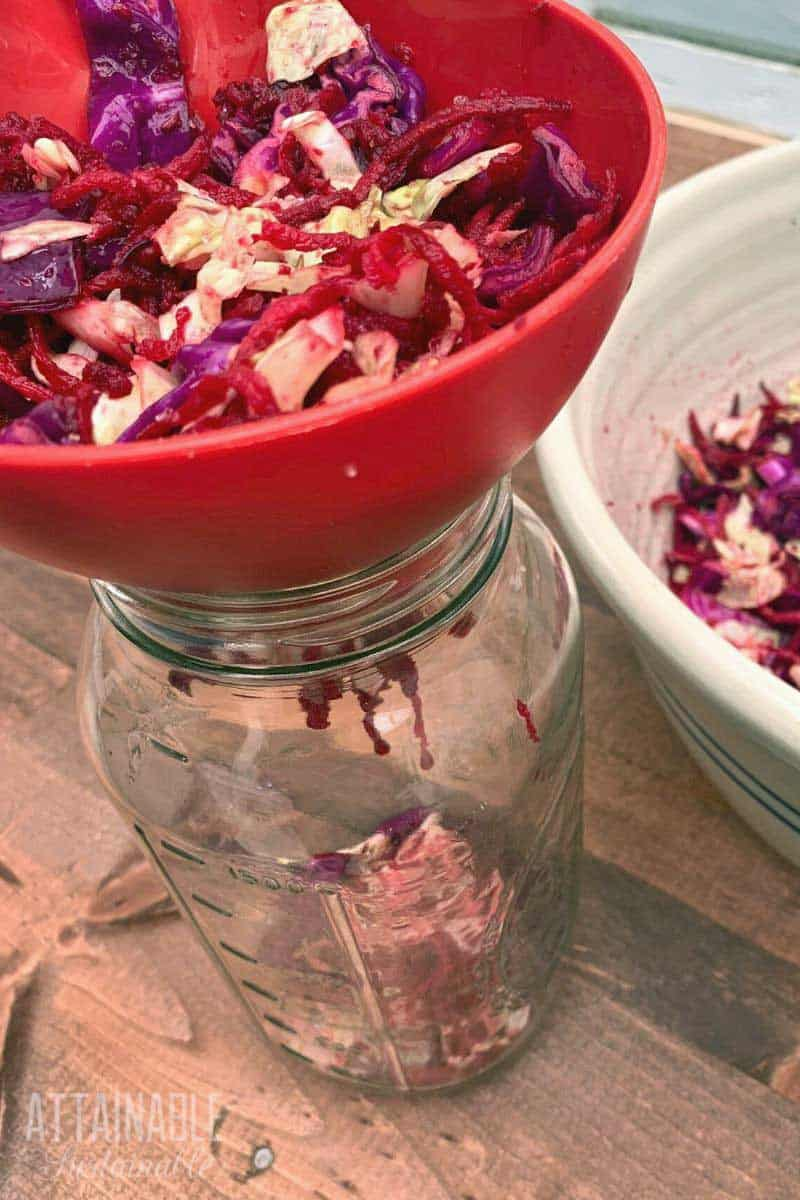 putting beet sauerkraut into a jar with a red funnel