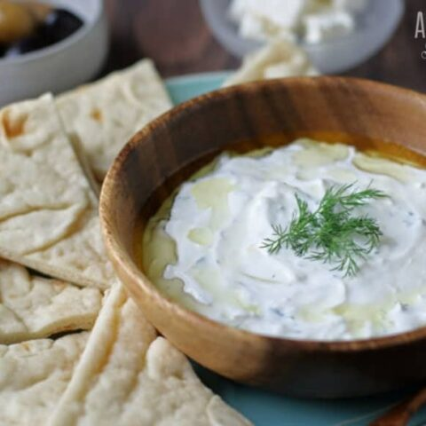 tzatziki in wooden bowl with pita chips