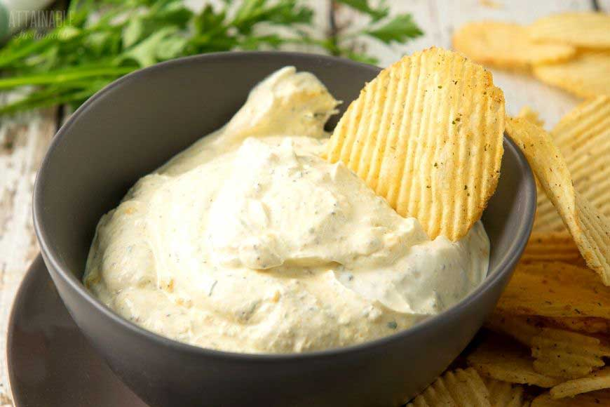 dip with ruffled chips in a brown bowl