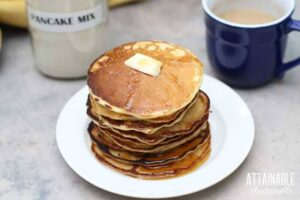 pancakes in a stack on a white plate with a pat of butter