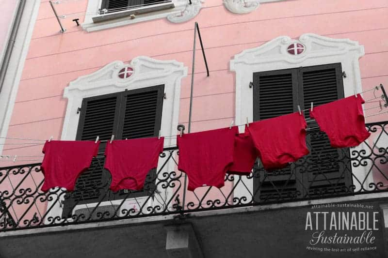 red tank tops handing on a clothesline against a pink building (Italy)