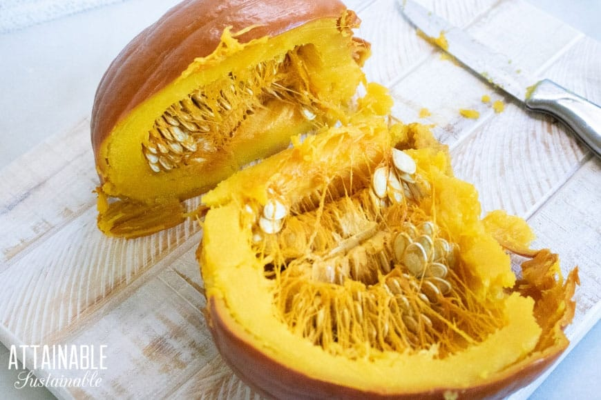 Whole cooked pumpkin cut in half, with seeds visible