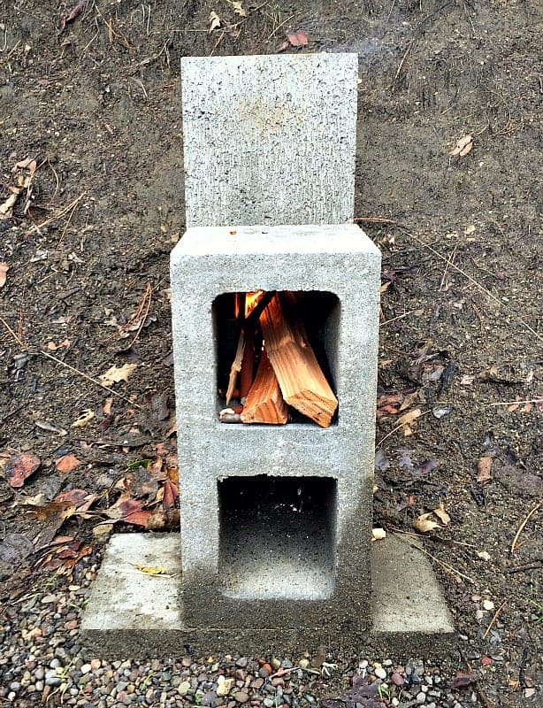 A rocket stove made of concrete blocks with kindling in upper cell.