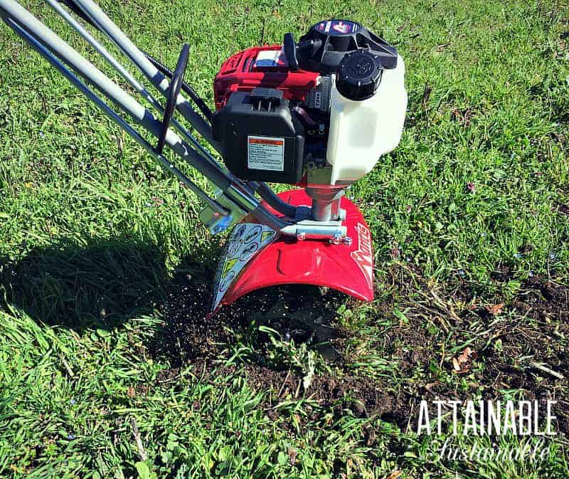Small, lightweight tiller on green grass