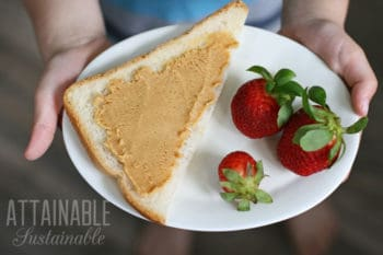 homemade peanut butter on a slice of bread with strawberries on a white plate