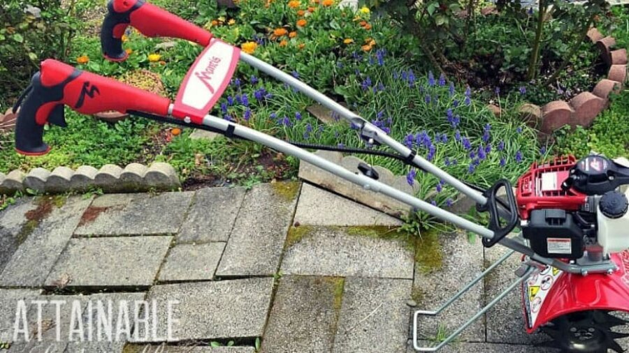 A small, lightweight rototiller (red) in front of orange and blue flowers.