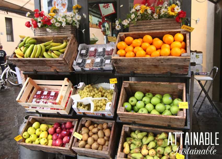fresh fruit stand with bananas, oranges, apples, and pears in wooden boxes