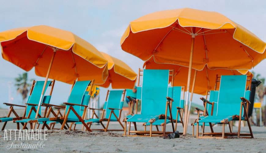 teal sand chairs with orange beach umbrellas on the beach