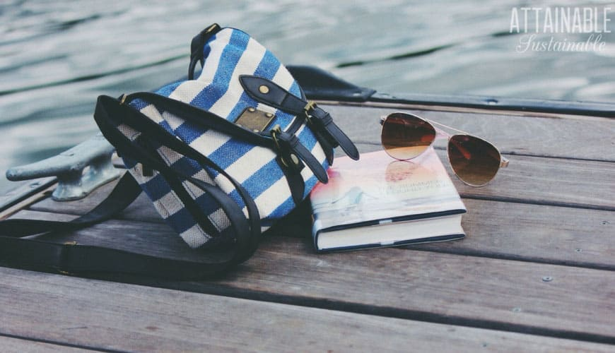 blue and white striped bag with book and sunglasses on a wooden dock.