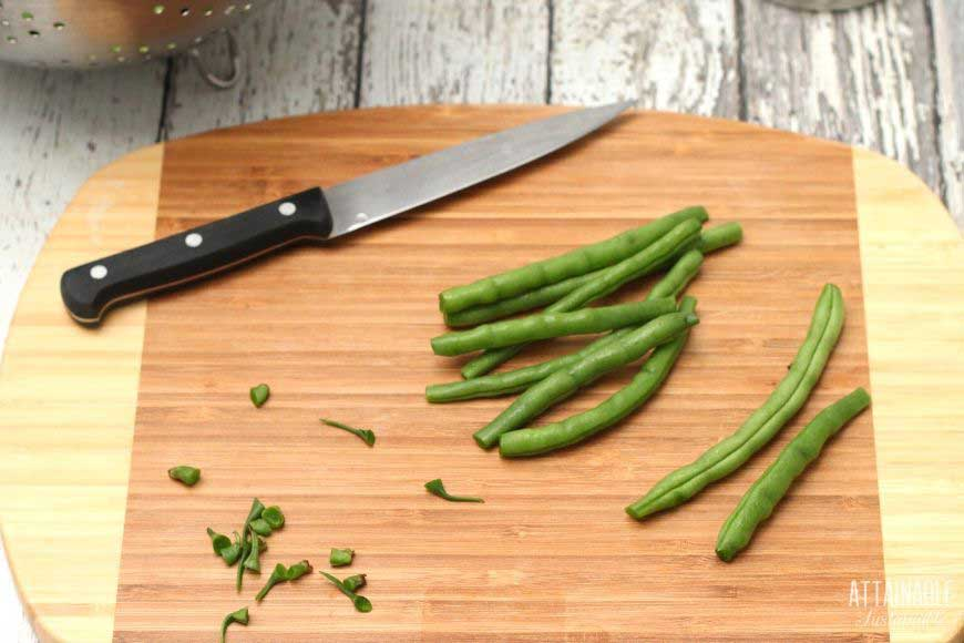 fresh green beans on a cutting board with a knife