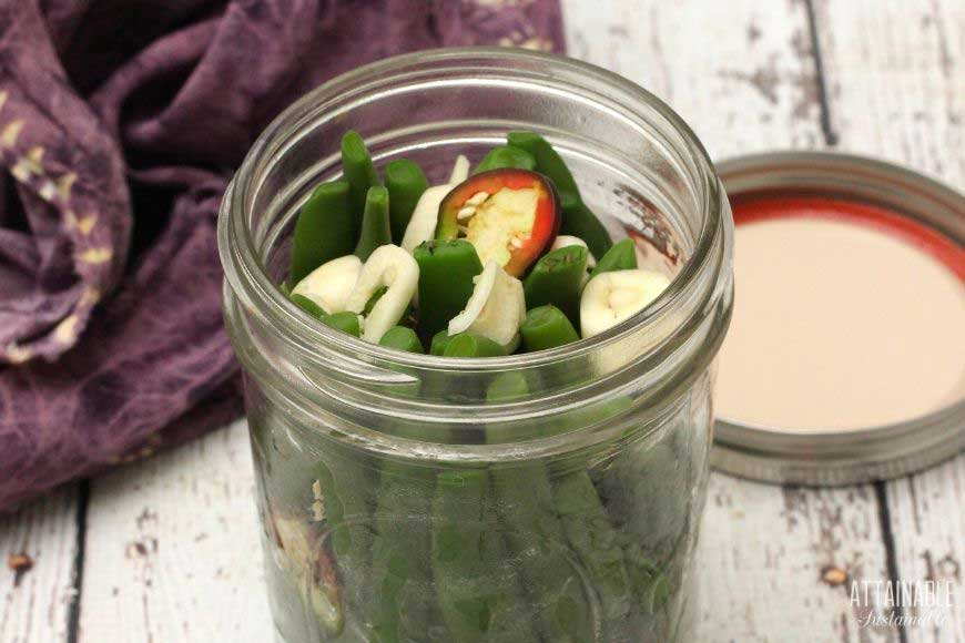 green beans in a glass jar with garlic and pepper slice