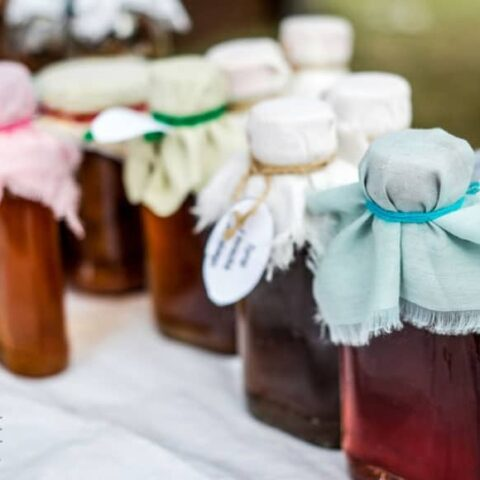 clear bottles with brown liquid, topped with pastel colored fabric