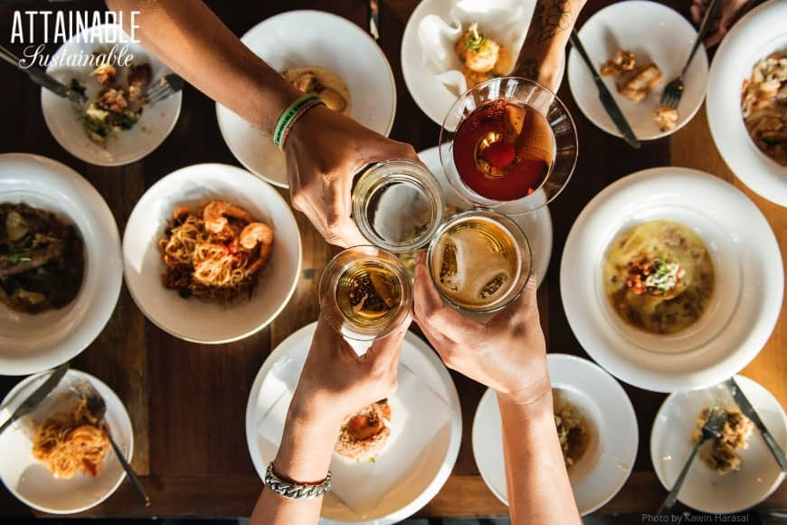 Four hands toasting with drinks from above, white plates full of food below