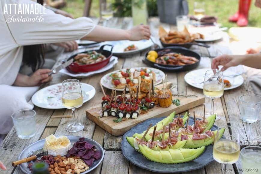outdoor gathering with food on a wooden table