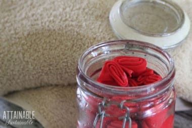 homemade dryer sheets (pink) in a glass jar with a tan towel behind