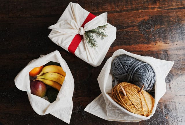 3 white bento bags on a wooden table, one christmas wrapped, one with fruit inside, one with yard skeins