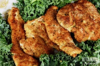 baked breaded chicken breast on a bed of kale