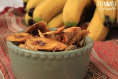 Dehydrated bananas stacked in a green bowl on a reddish striped tablecloth. Fresh bananas in the background