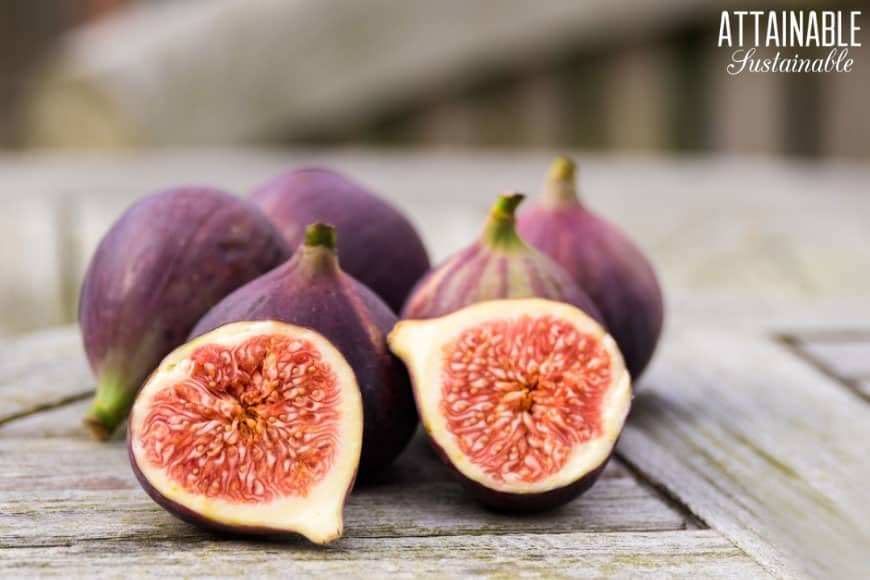 figs on a wooden table, one cut in half showing pinkish flesh