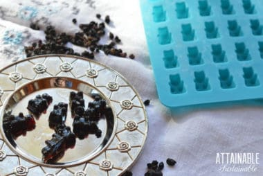 elderberry gummies on a silver plate, with a blue silicone mold