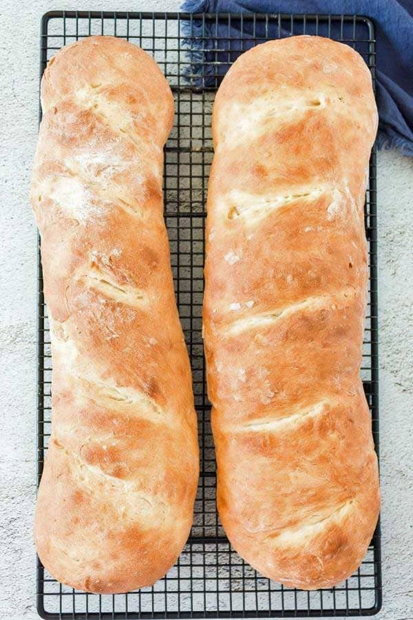 two loaves of browned french bread cooling on a wire rack