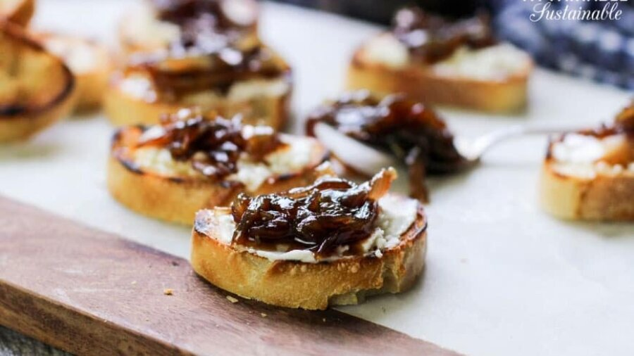 toasted baguette slices spread with goat cheese and balsamic onion jam