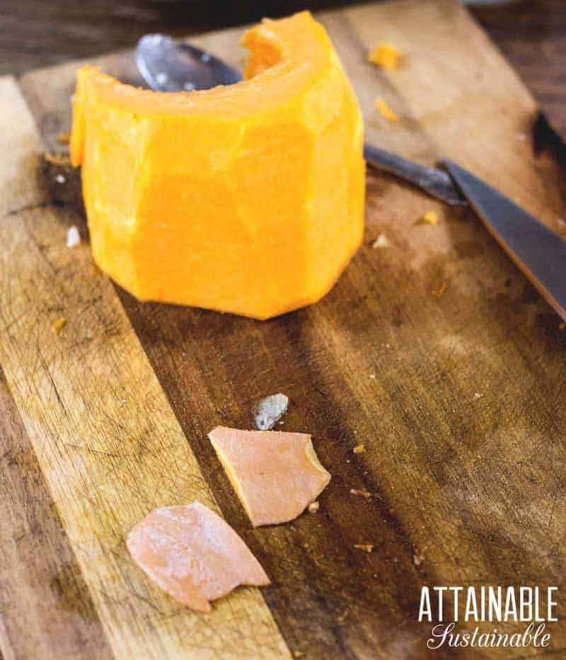 peeled raw pumpkin on a cutting board with a knife