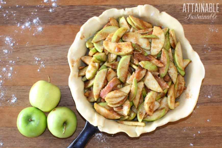 sliced apples in a pie dough lined cast iron skillet