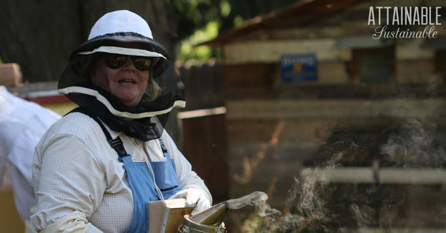 woman in beekeeping gear doing fall chores