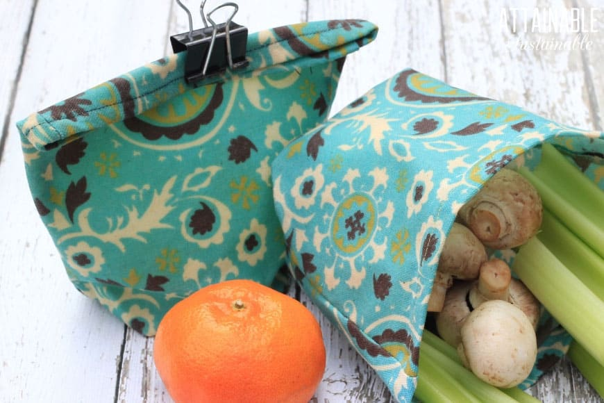 DIY reusable snack bags in a teal print, with celery, mushrooms, and a tangerine