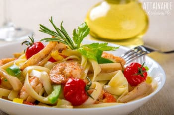 white plate with fettuccine pasta, tomatoes, basil